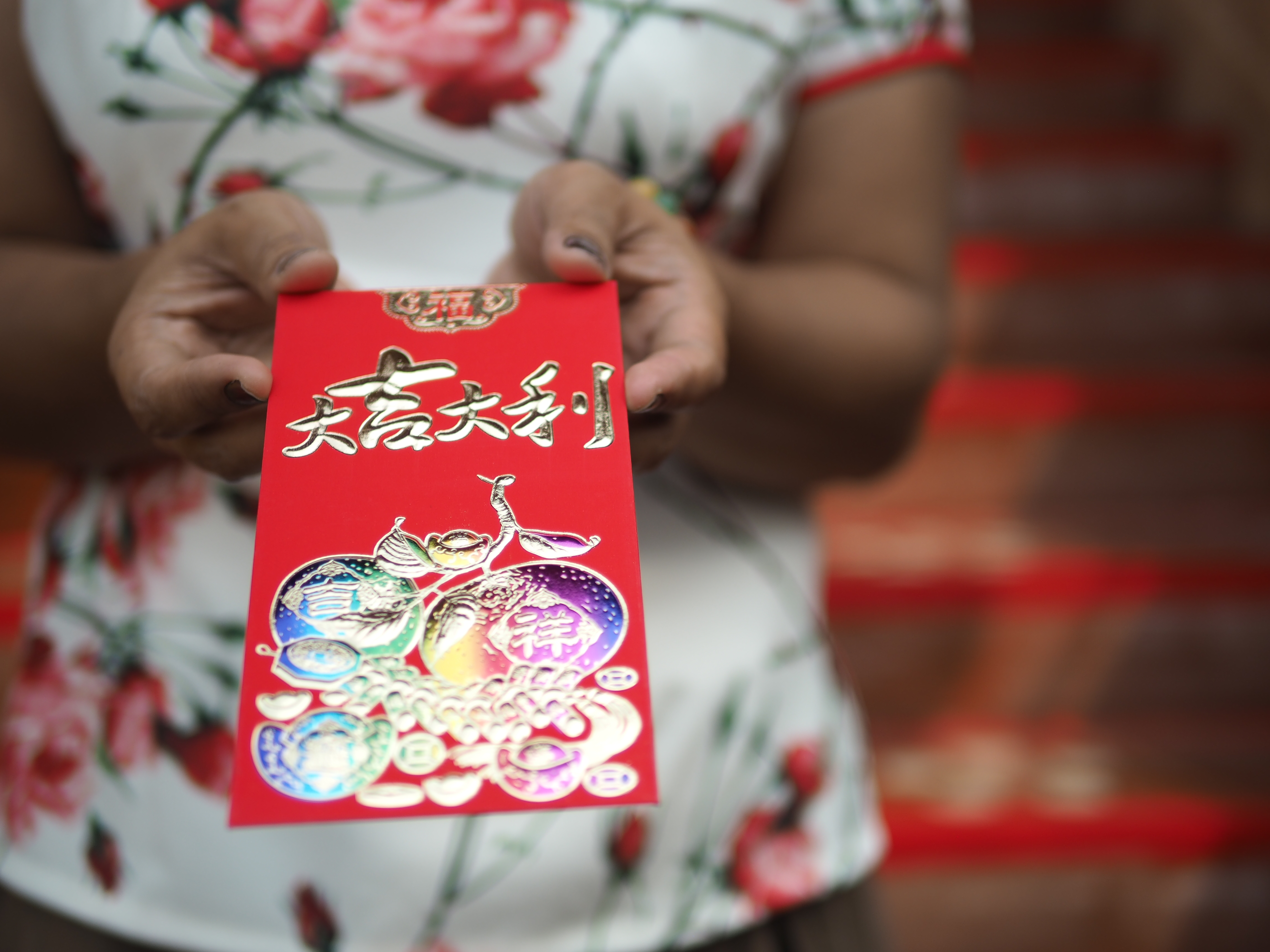 Woman in a qipao holding out a red envelope with both hands.