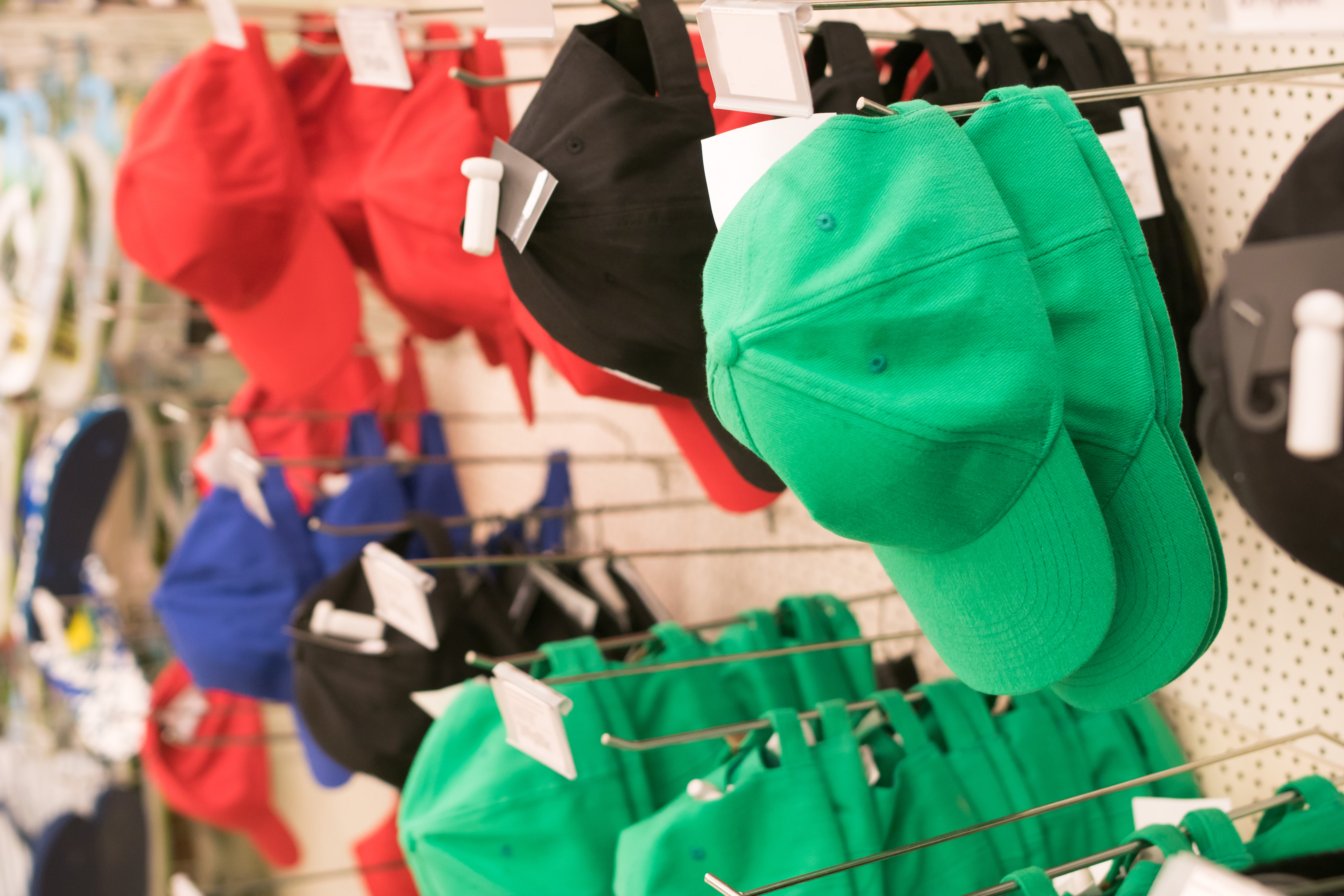 Green, red, and black baseball caps hanging on hooks against a white wall.