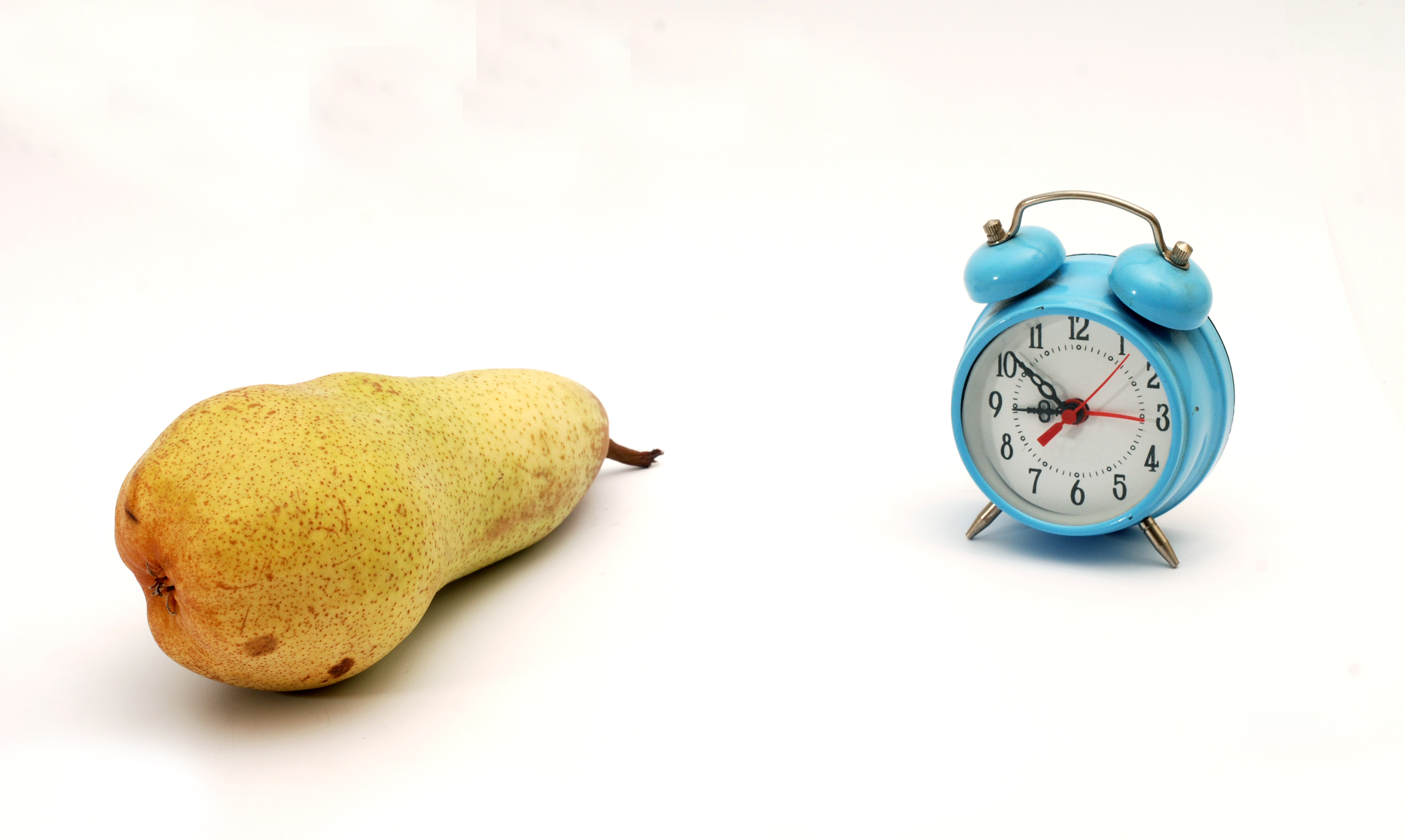 Pear and a clock on a white background.