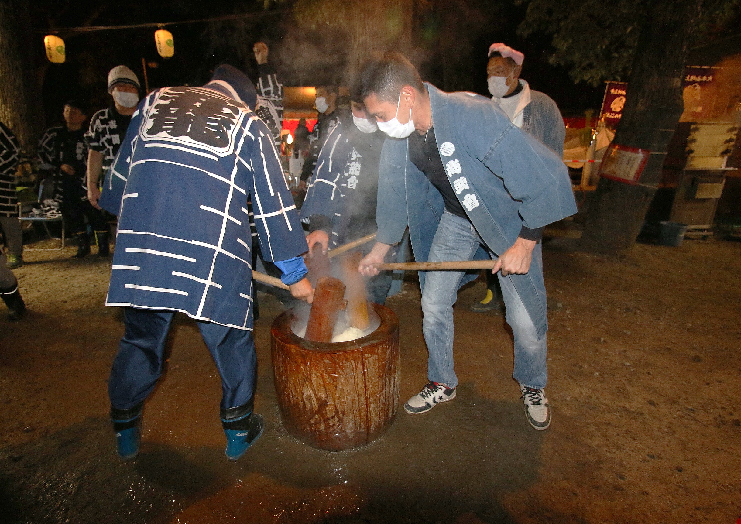 Men pound mochi with a mortar and pestle