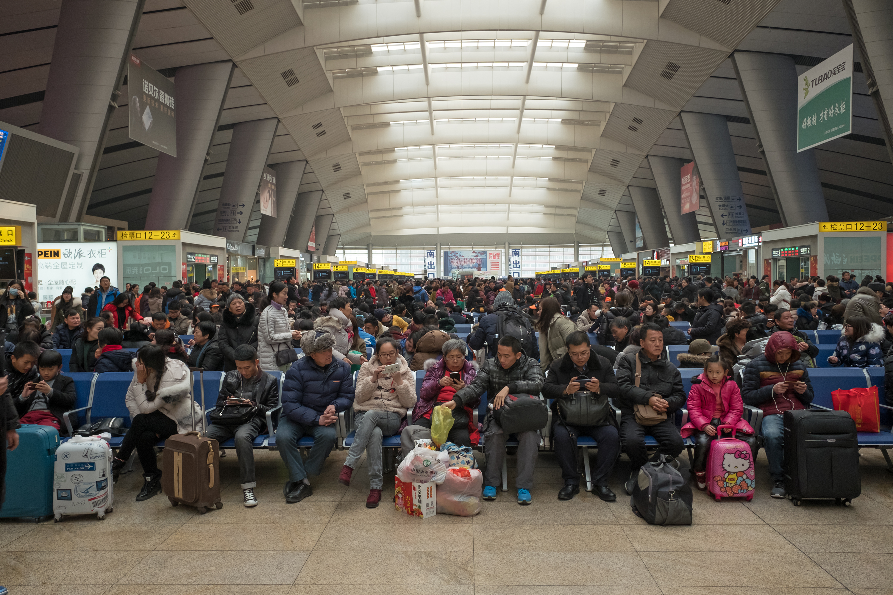 travelers wait in crowded Beijing train station
